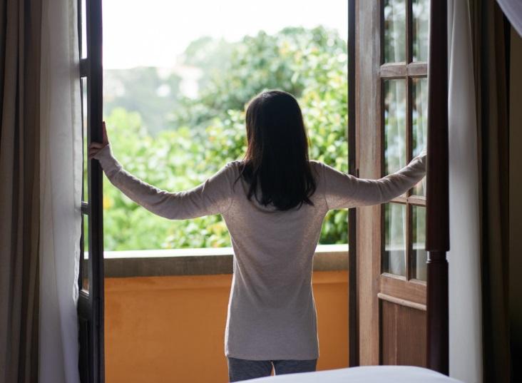 Femme qui ouvre ses fenêtres