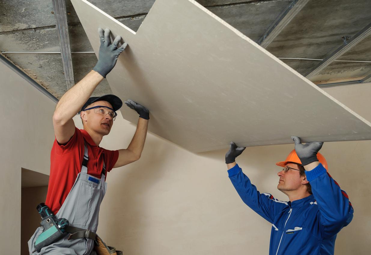 Des ouvriers qui posent des plaques de platre
