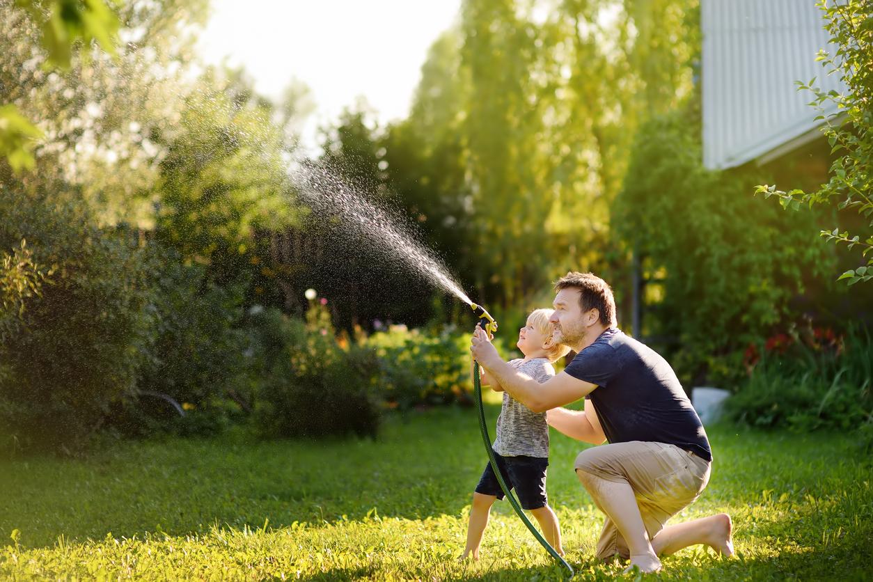 Un père et son fils joue avec le tuyau d'arrosage