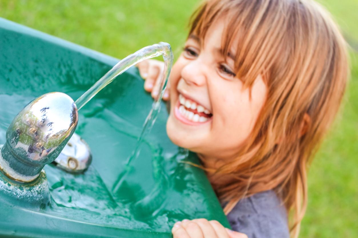 Une petite fille qui boit à la fontaine