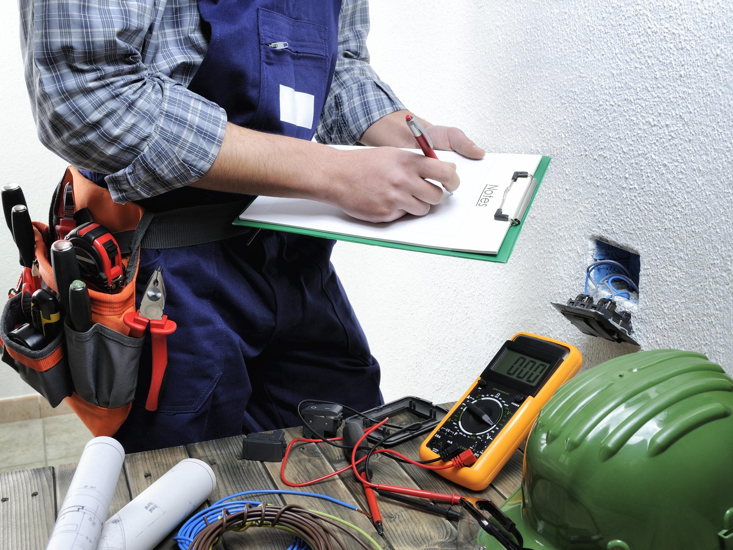 Un électricien s'occupant d'une prise électrique