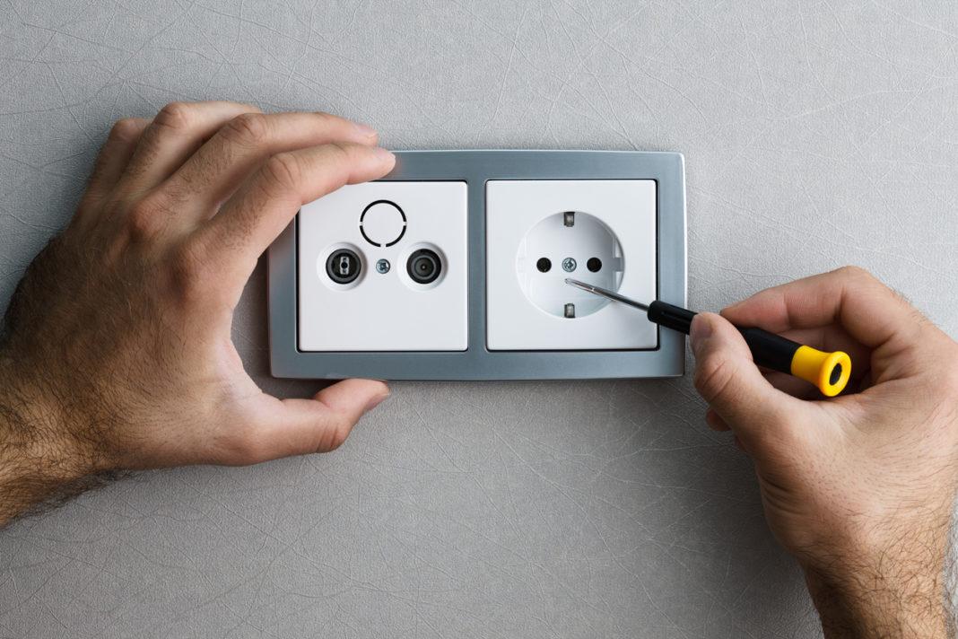 Une prise électrique avec un tournevis