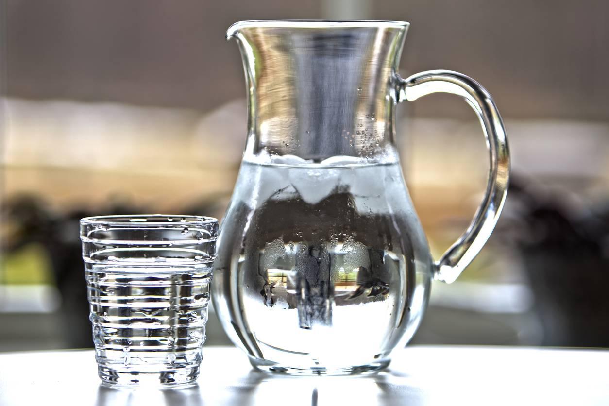 Une carafe d'eau avec un verre à coté