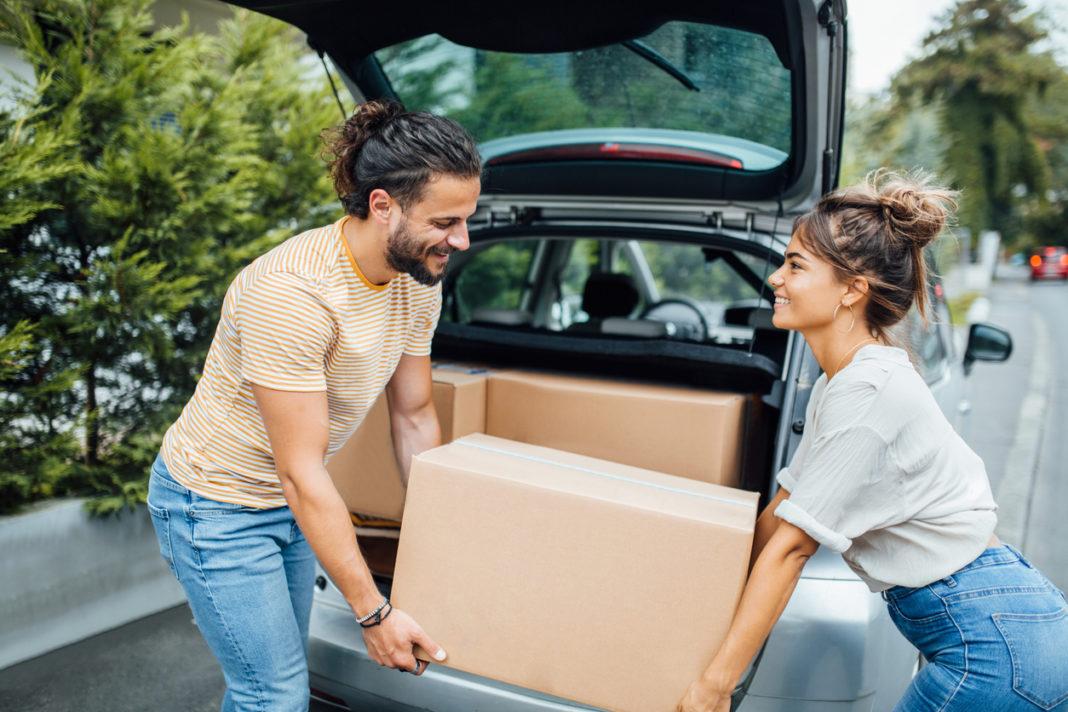 Un couple rangeant ses cartons de déménagement dans leur voiture
