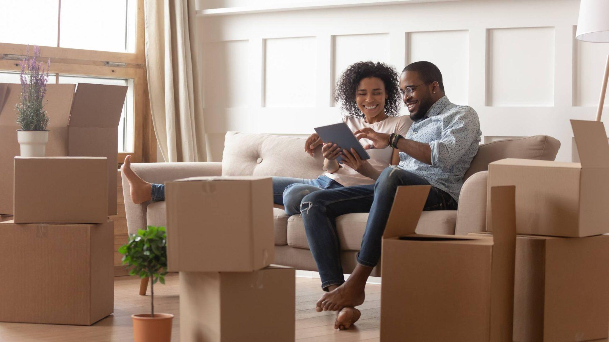 Un couple assis sur un canapé avec des cartons de déménagement autour