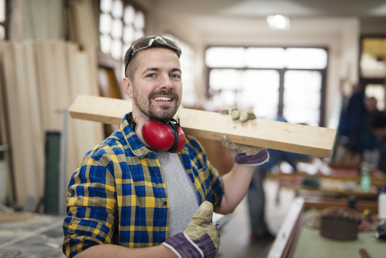 Un artisan portant une planche en bois avec le sourire