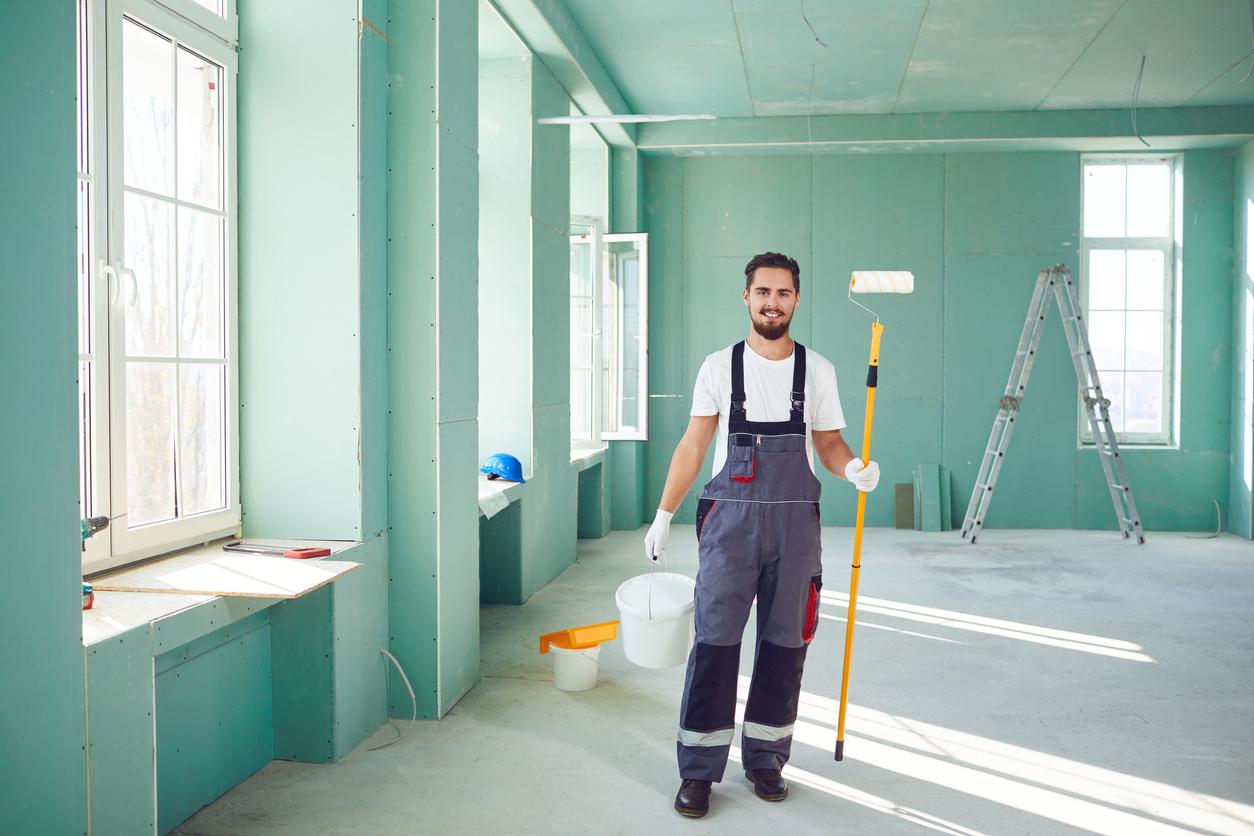 Un homme qui peint les murs d'une maison