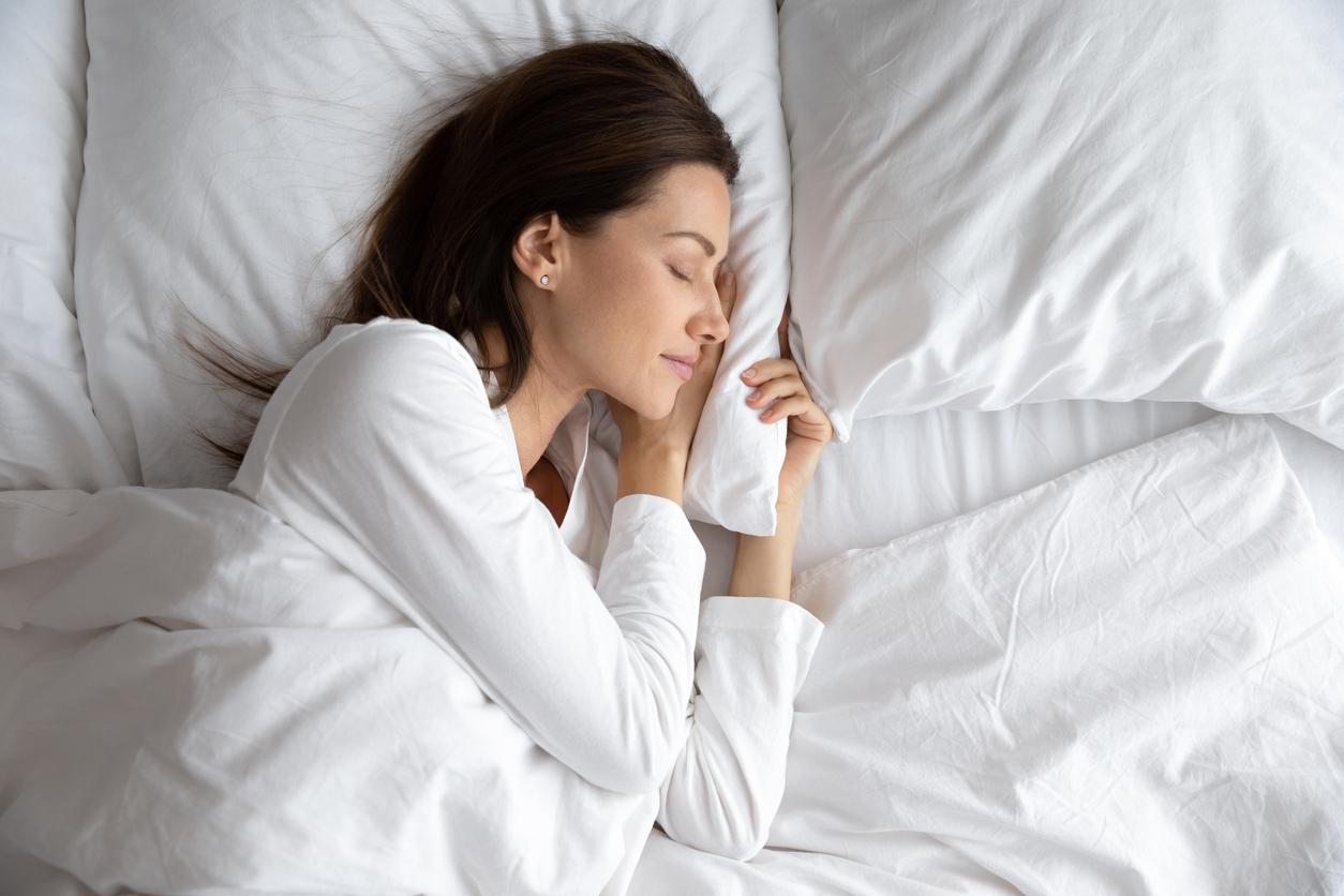 Une femme entrain de dormir dans un lit sous une couette