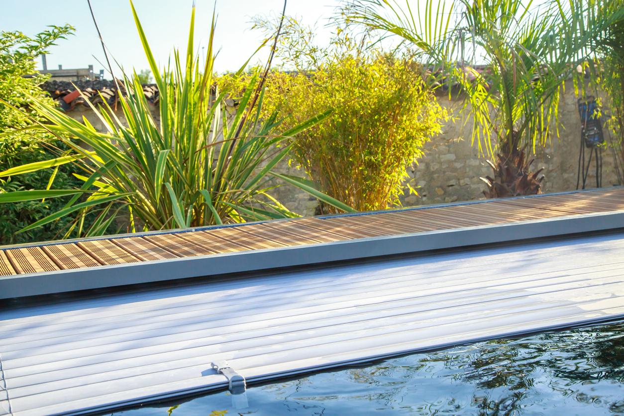 un volet roulant sur une piscine avec une terrasse en bois