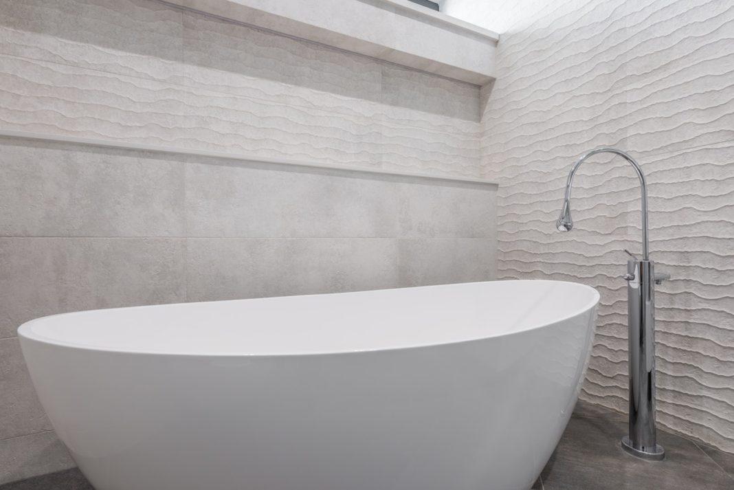 baignoire blanche au centre d'une salle de bain pierre naturelle