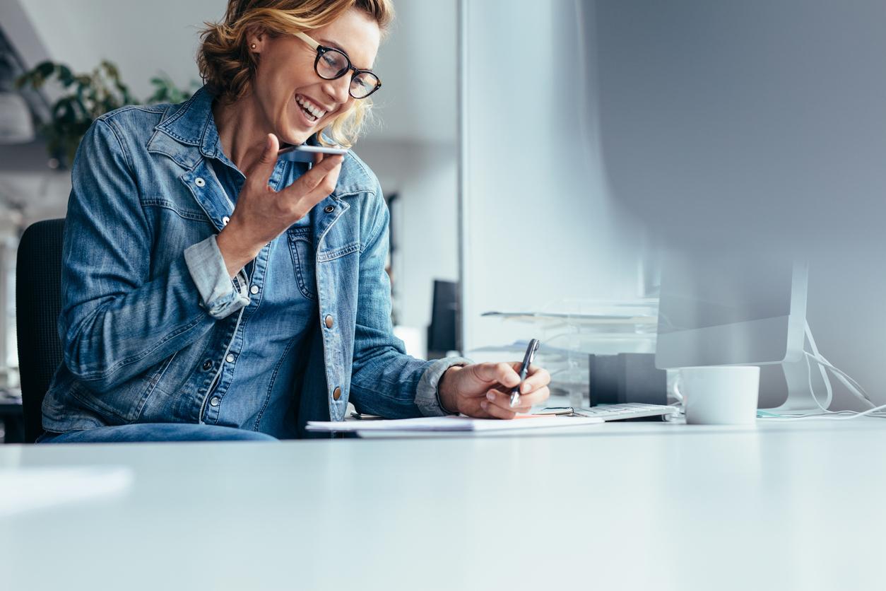 femme souriante au téléphone signant un document