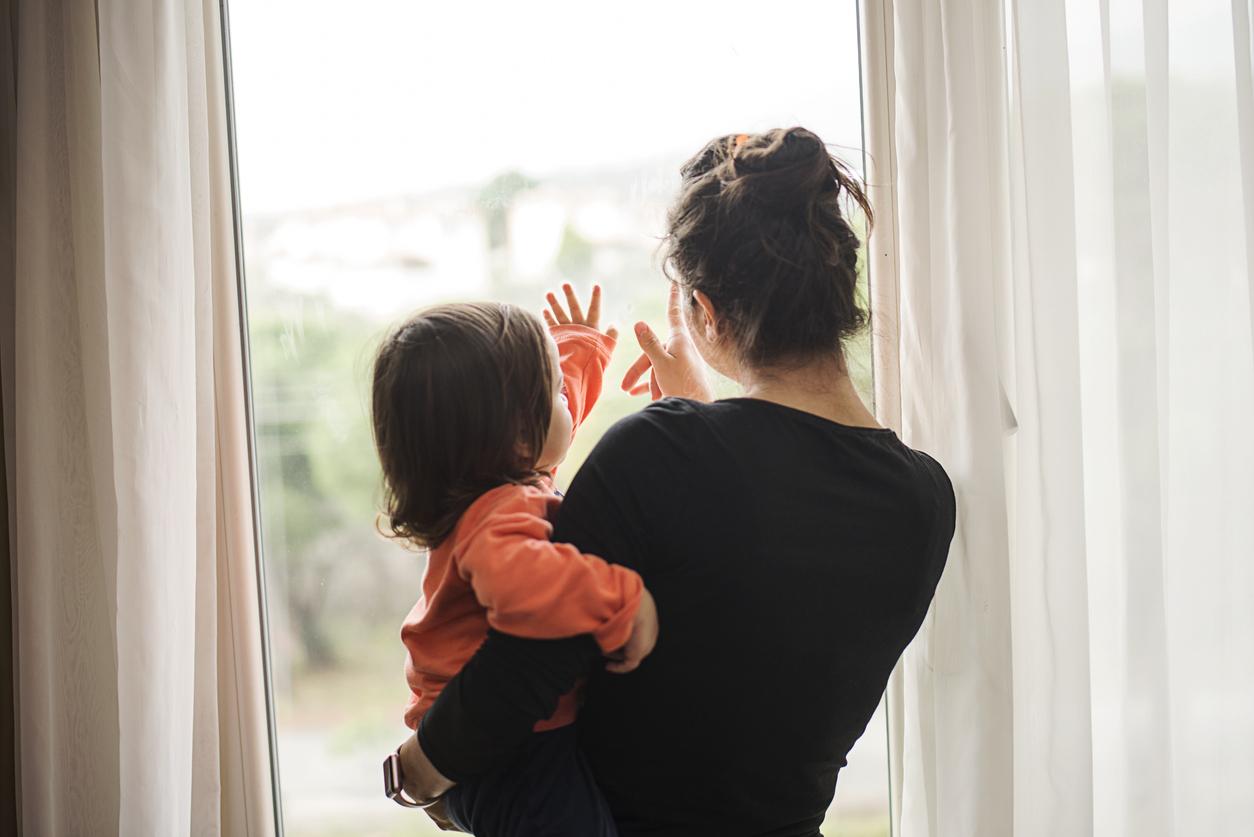 enfant bras maman devant une fenêtre fermé