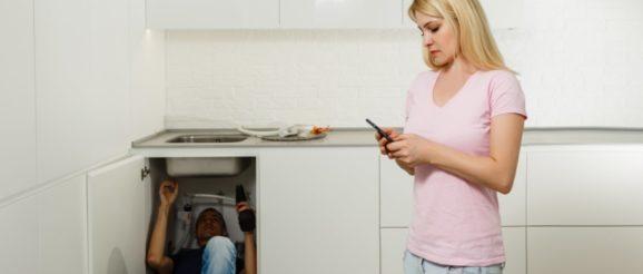Plombier sous l'évier et femme qui tient son téléphone