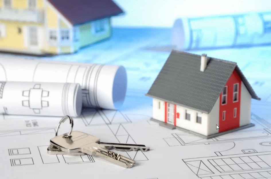 Une petite maison et des clés sur un plan de construction