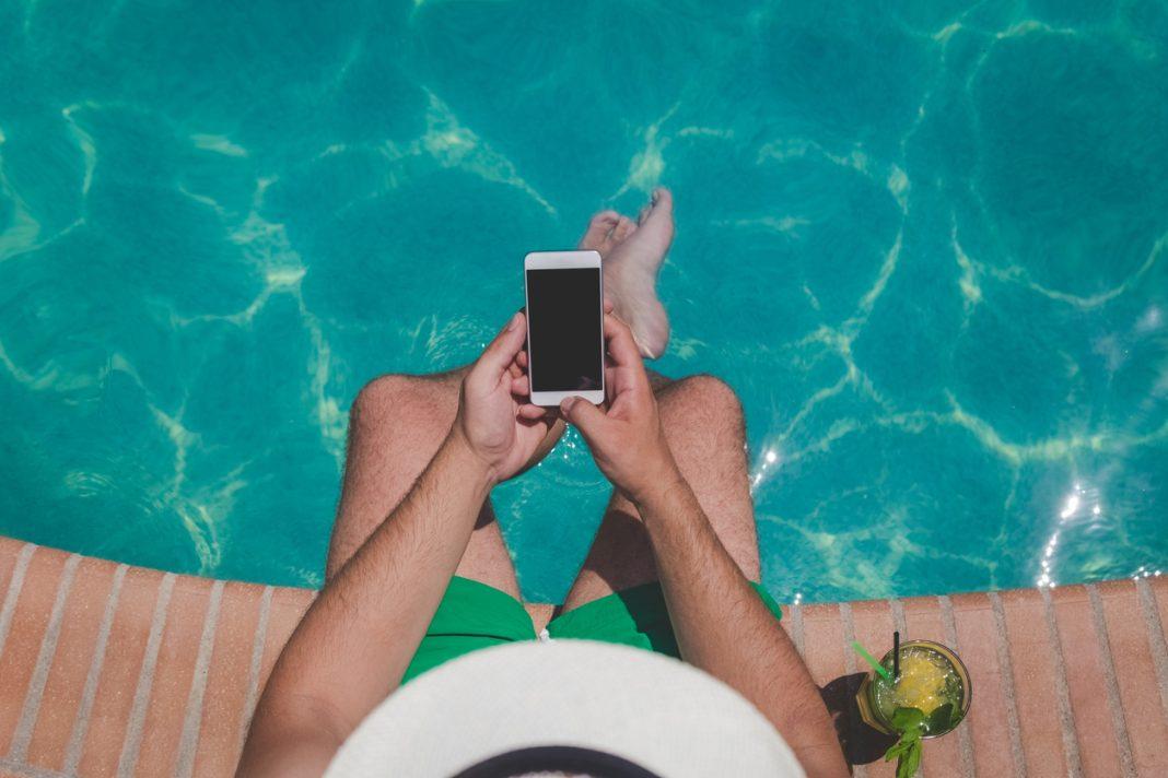 Un homme les pieds dans l'eau de sa piscine avec son téléphone à la main et un cocktail