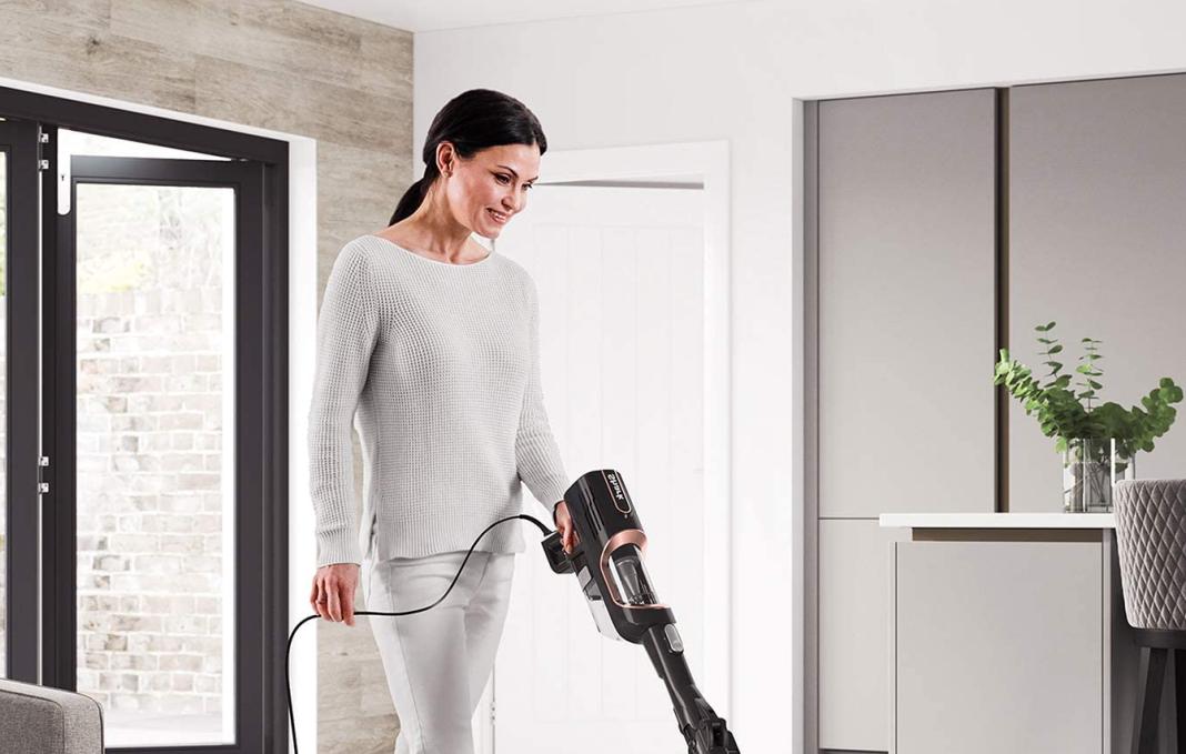 femme souriante passe aspirateur dans son salon éclairé