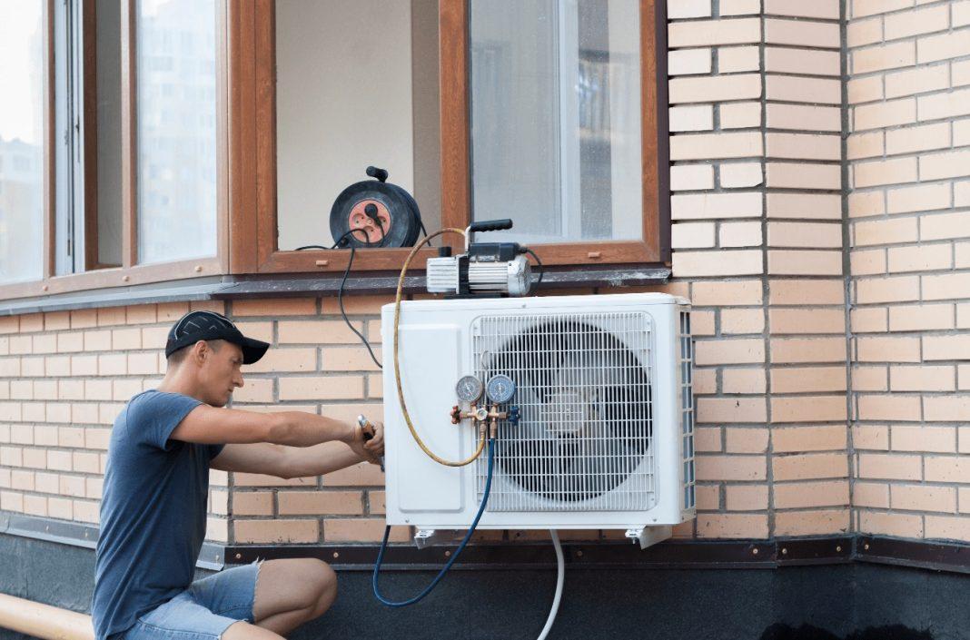 homme installe pompe à chaleur extérieur maison